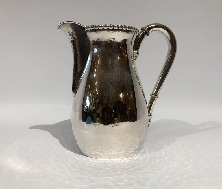Beautiful water jug in hammered hallmarked silver and simple pearl edge.