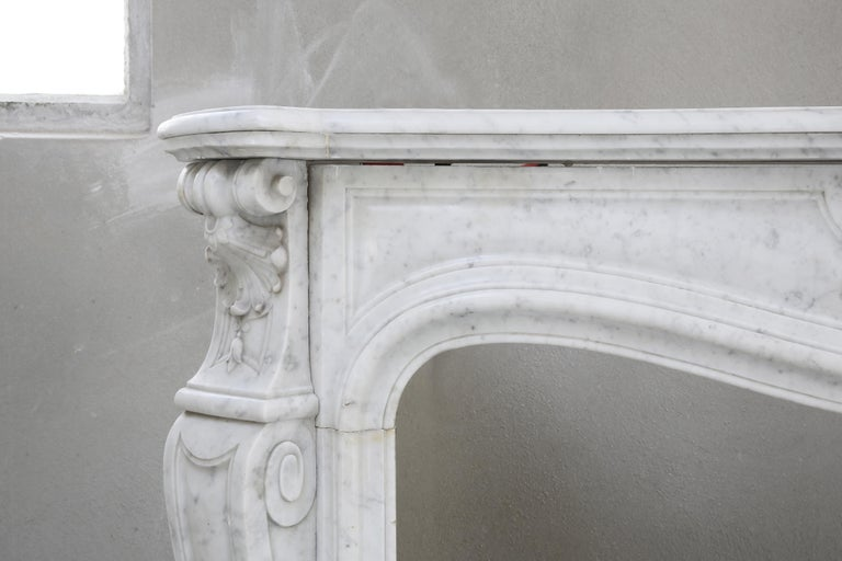 Very nice white marble fireplace from carrara marble. Carrara is a place in Italy that is world-famous because of the beautiful marble that comes from the quarries. The chimney is flanked with 'trois scallops', or three shells. In the middle is the