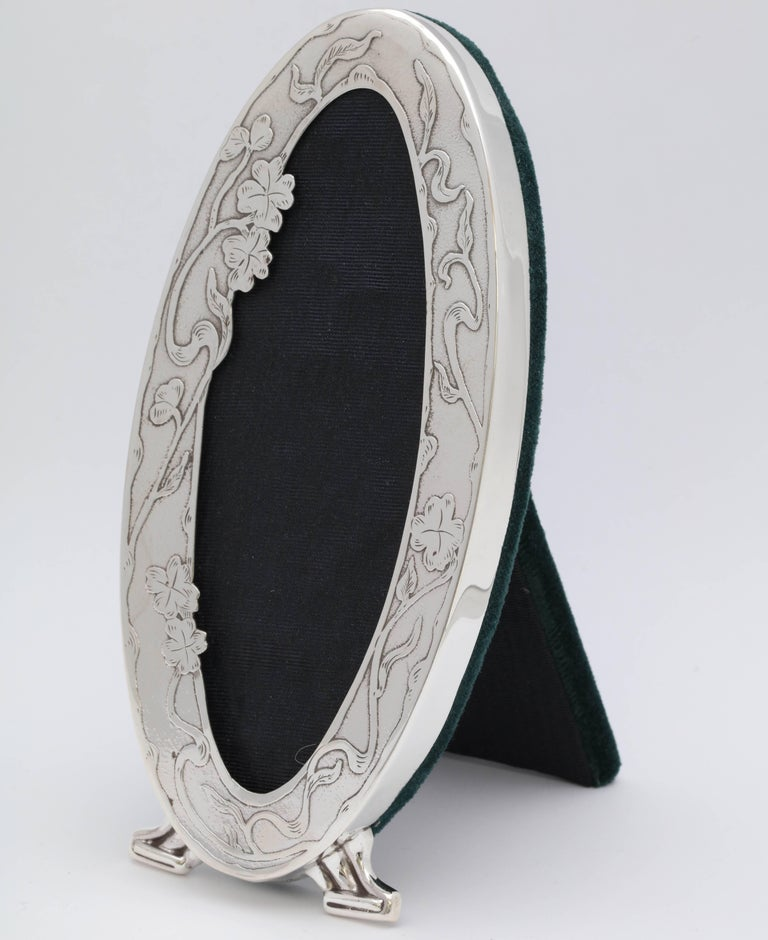 Beautiful and rare, Art Nouveau, footed sterling silver picture frame, Simpson, Hall, Miller and Co., Wallingford, Connecticut, circa 1895. Frame is very lightly hammered in texture and is designed with lovely Art Nouveau flowers whose stems whip