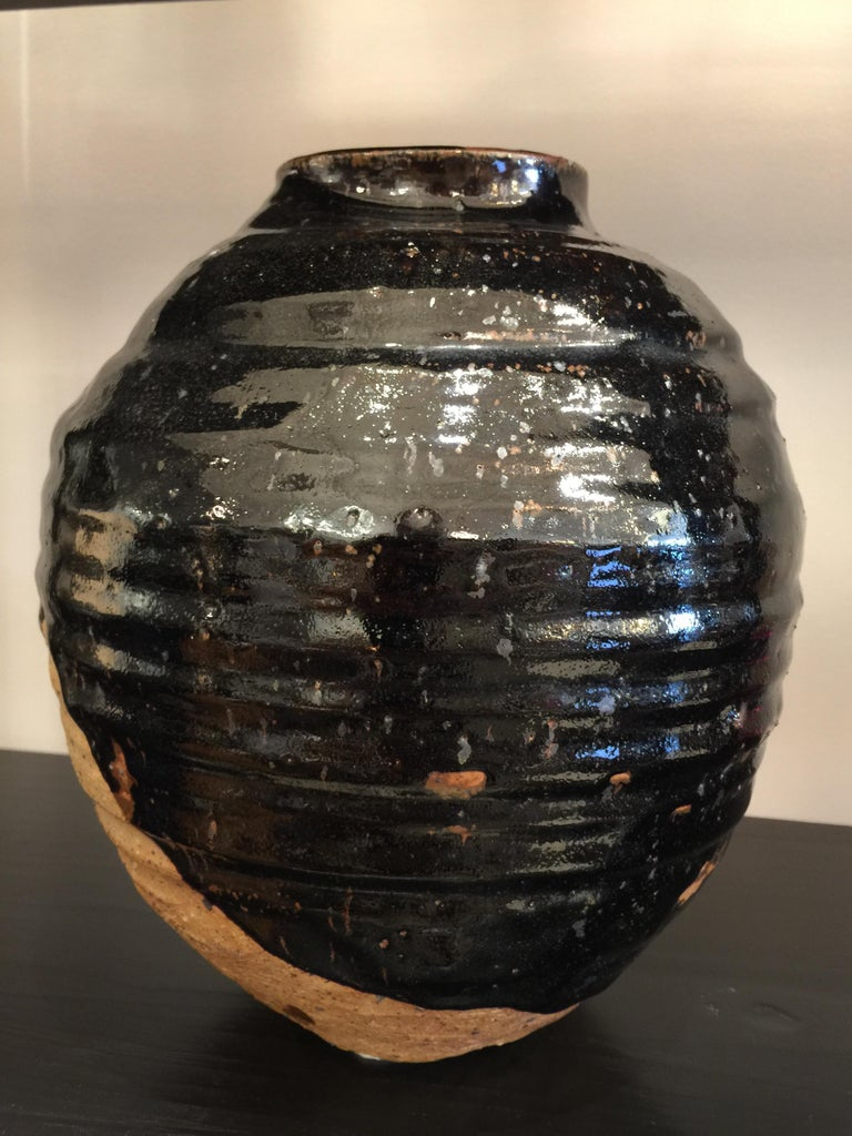 This is an extremely well made and stylish black glazed over natural earthenware vase.