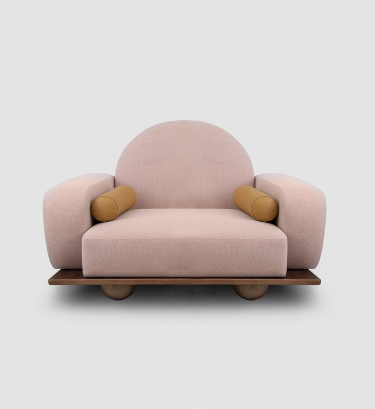 Beice armchair is designed to mimic the feeling of sitting on a cotton candy cloud. The combination of its color, arc shaped back rest, round edges and sphere walnut feet creates a dreamy, tender design. Beice is entirely handcrafted and