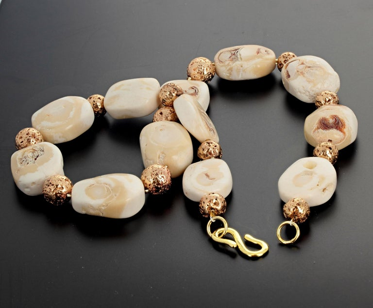 This lovely 21 inch long Beige Coral necklace is enhanced with gold plated round fascinating lava beads set with an easy to use gold plated hook clasp.  The Corals are approximately 30 mm x 22 mm.  The largest goldy beads are approximately 13 mm.