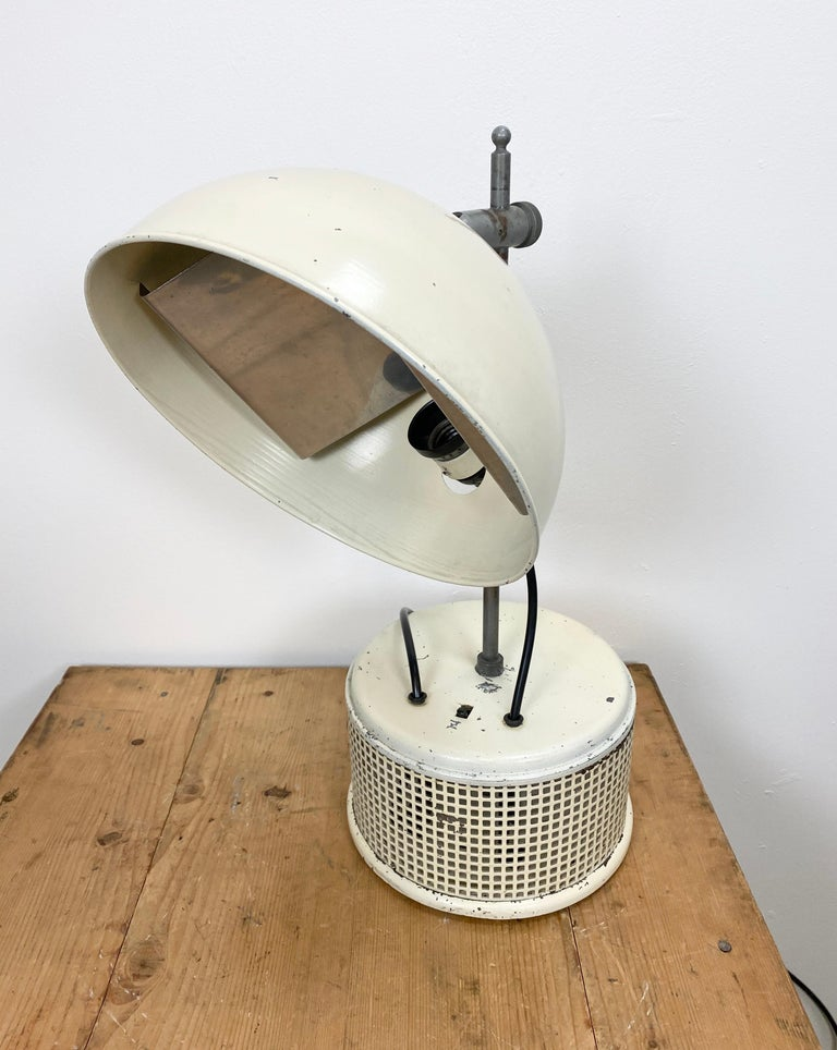 This beige industrial iron table lamp was made in former Czechoslovakia during the 1950s. It has an adjustable shade, a metal base with a switch, an original bakelite socket for E 27 light bulbs and new wire. The diameter of the lampshade is 27 cm.