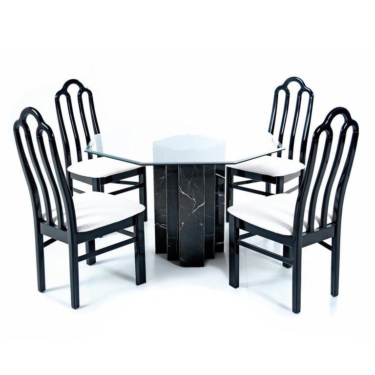 This handsome dining table has a regal presence with it's stately, yet sexy, black marble base. The vintage 1980s dining set has resembles work by Carlo Scarpa. The sleek dining set comes complete, as pictured with a dining table and four chairs.