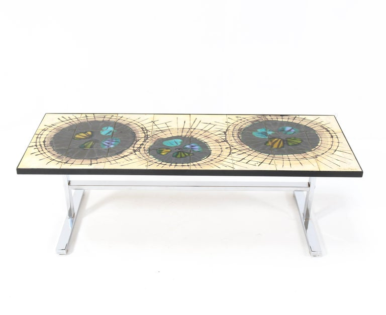 Wonderful Mid-Century Modern coffee table. Design by Julliette Belarti. Striking Belgium design from the 1960s. Chrome plated frame with ceramic tile top. Marked on the table top. In good original condition with minor wear consistent with age