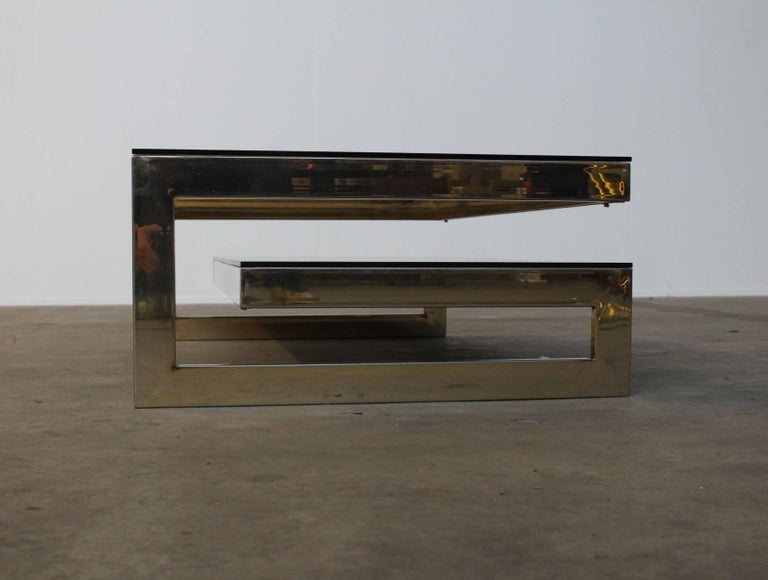 Two Identical available. Stunning architectural two-tiered rectangular gold plated 23 carat coffee table by Belgo Chrome, in Maison Jansen style, circa 1970. A very eye-catching Minimalist yet Hollywood Regency design. On the bottom level a smoked