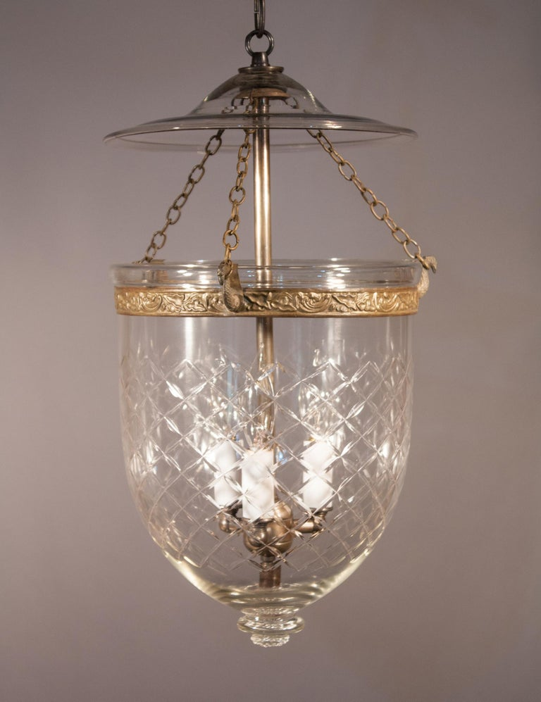 An authentic 19th century English bell jar lantern with lovely form and an etched diamond motif. This circa 1870 pendant features its original embossed brass band and smoke bell. The quality of the hand blown glass is excellent, with a few visible