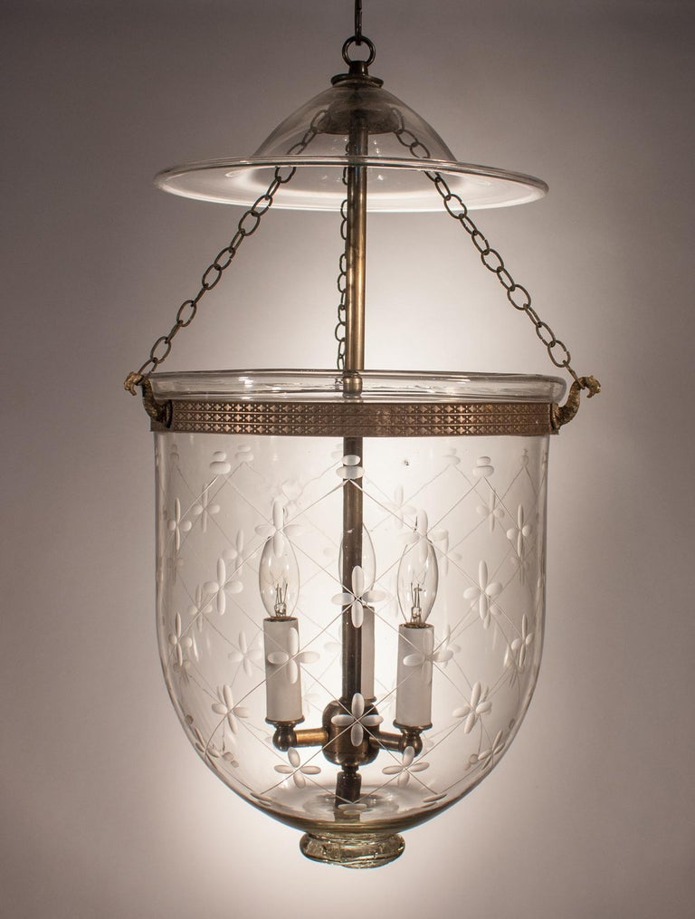 A 19th century English bell jar lantern with lovely form and an etched climbing trellis design. This circa 1890 handblown glass pendant is in very good condition and features its original smoke bell, chains, and a unique pontil. The brass band,