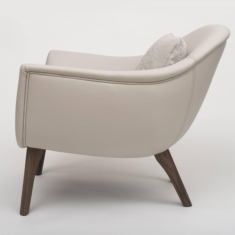 This sophisticated armchair is the epitome of elegance. The barrel-shaped frame has wide, embracing arms, and is upholstered with Fine leather in a versatile ice-white color. The tapered, conical feet are made of solid Canaletto wood with a natural