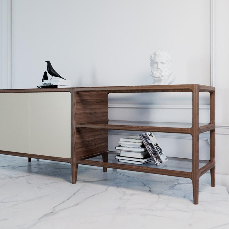 The skillful combination of prized details on an essential ash frame makes this sideboard a one-of-a-kind piece. Its solid structure stands on six feet and comprises an open shelving unit with two glass shelves and a regular unit featuring two doors