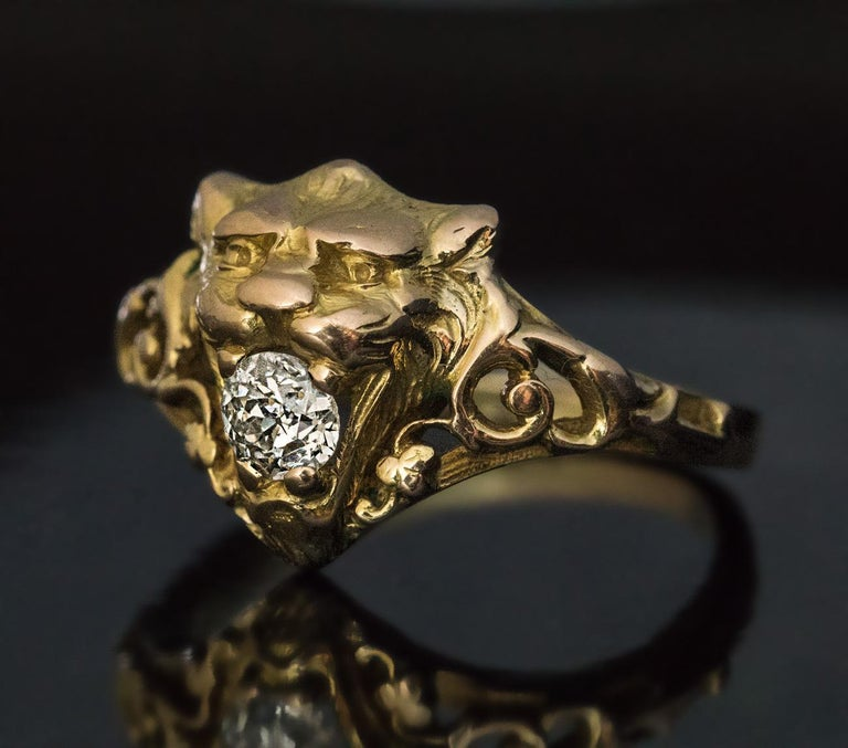 Circa 1890  This antique 14K gold unisex ring is finely modeled as the head of a lion with a sparkling bright white old mine cut diamond in its mouth. The lion is flanked by openwork shoulders with scrolling designs.  The diamond measures 4.68 x