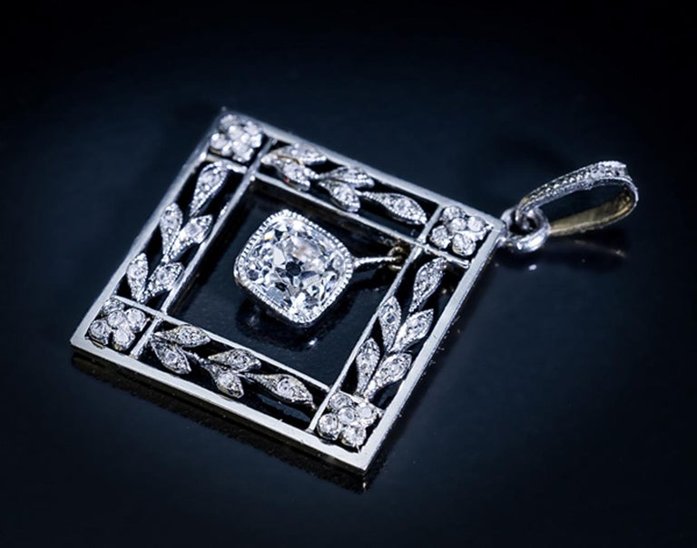 Austria, Vienna, circa 1905  This elegant antique garland motif pendant from the Edwardian era is crafted in platinum over 14K gold. The pendant features a sparkling old cushion cut diamond (approximately 0.86 ct, H color, VS1 clarity) set in a