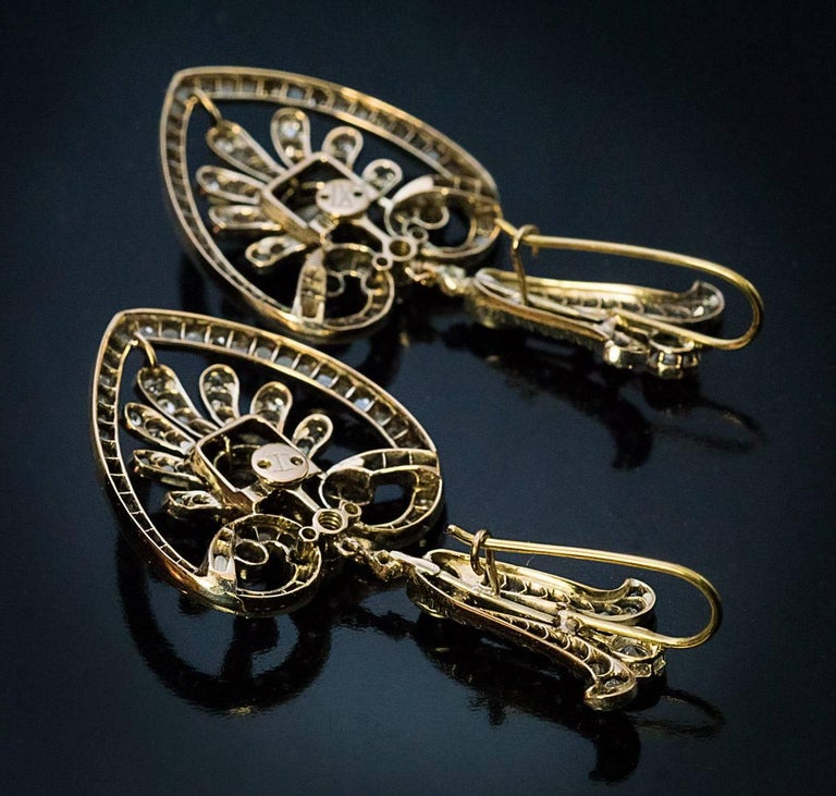 Circa 1880  Finely handcrafted in silver-topped gold antique openwork earrings are embellished with old European, old mine and rose cut diamonds.  Estimated total diamond weight is 5 carats.  Total length with earwire 55 mm (2 1/4 in.)  Width 26 mm