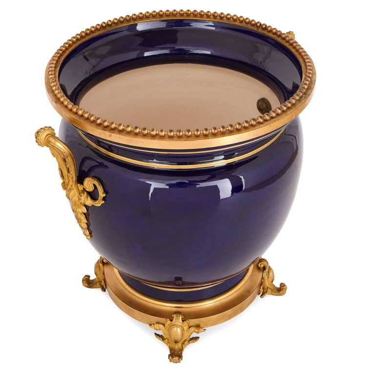 While this jardinière dates from the late 19th century, it feels strikingly contemporary in its combination of refined cobalt blue porcelain and sleek gilt bronze (ormolu) mounts.  The jardinière's wide body is decorated with gilt bands around its