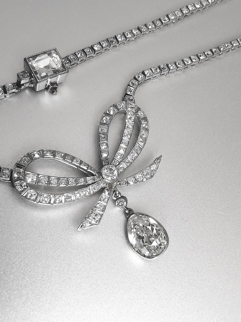 Belle Epoque Diamond Platinum Bow Pendant Necklace. Old mine cut Pear shape Diamond estimated over 1.00 carat in our opinion. Clasp set by a Square cut Diamond estimated over 1.00 carat in our opinion. Circa 1920.  Total length: approximately 17.00