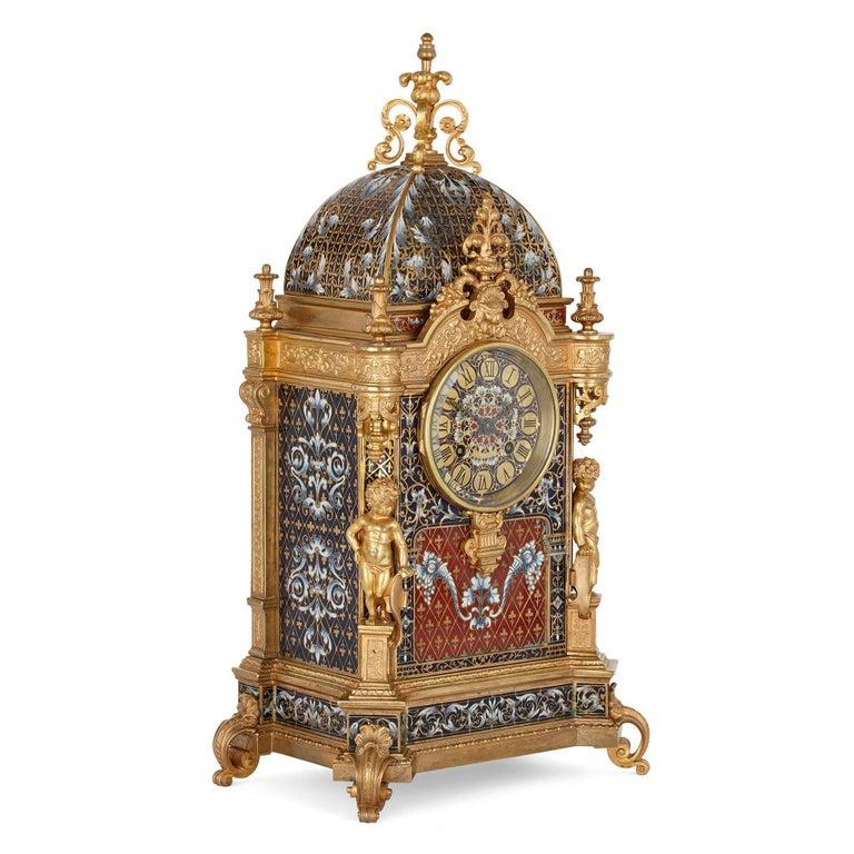 Belle Époque period gilt bronze and enamel clock set French, late 19th century Measures: Clock: Height 46cm, width 23cm, depth 15cm Vases: Height 29cm, diameter 11.5cm Candlesticks: Height 26.5cm, diameter 10cm  This superb clock set comprises