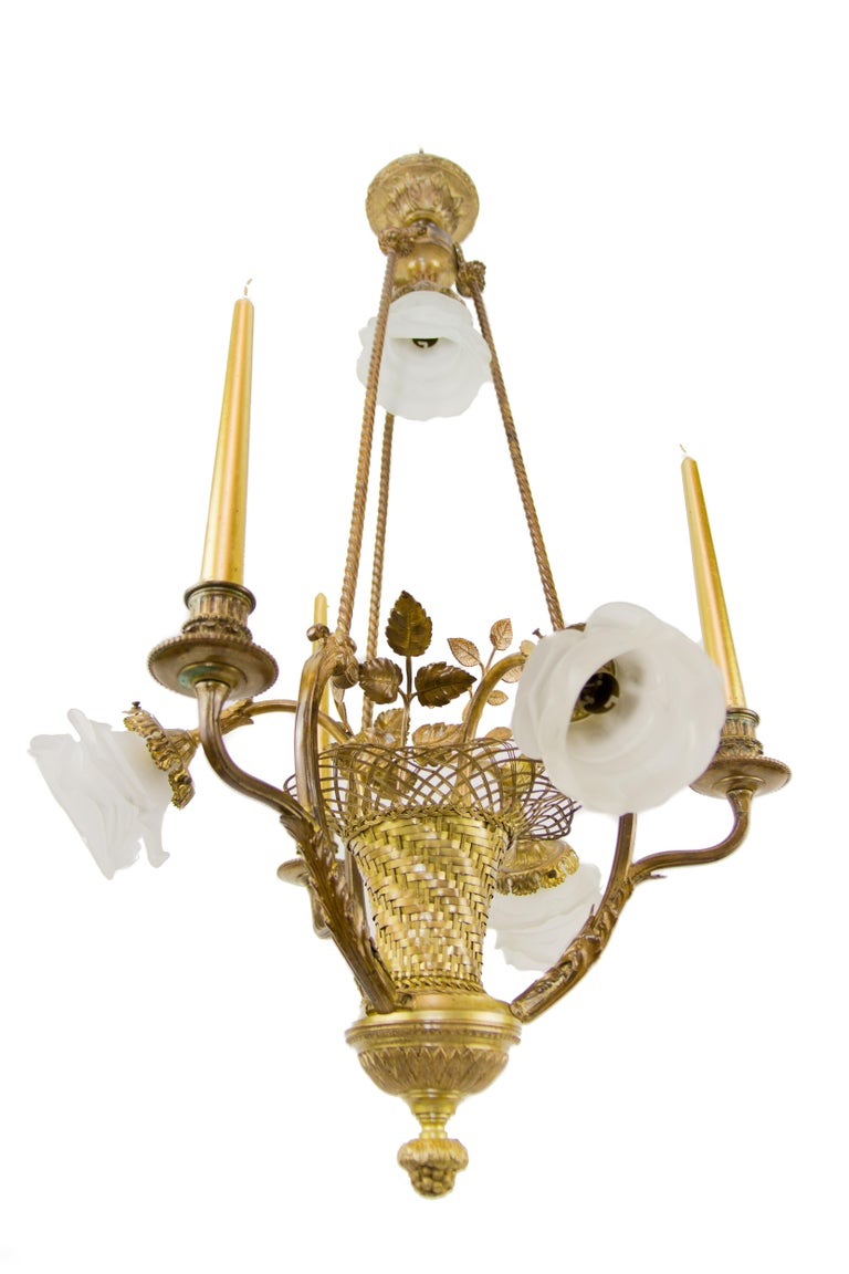 French Belle Epoque bronze woven basket chandelier. Three arms are candle holders, three arms and one light on top have B22 sockets with new wiring, frosted glass flower shaped shades. Measures: Total height is 33.4 inches / 85 cm; diameter 19.7