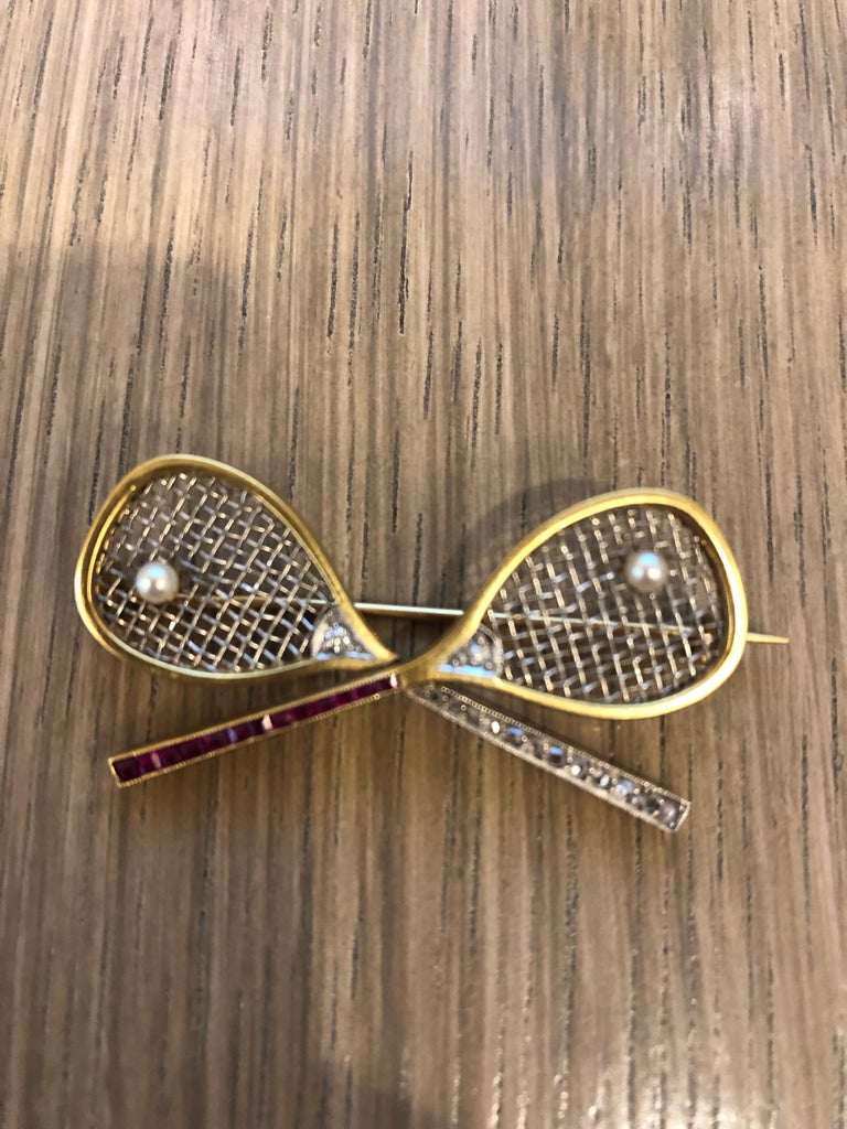 A gold and platinum brooch with ruby, diamond and pearl. The fetching sporting brooch features two tennis rackets, cleverly executed in both platinum and gold for various parts of their hardware, and studded with diamond and ruby for their