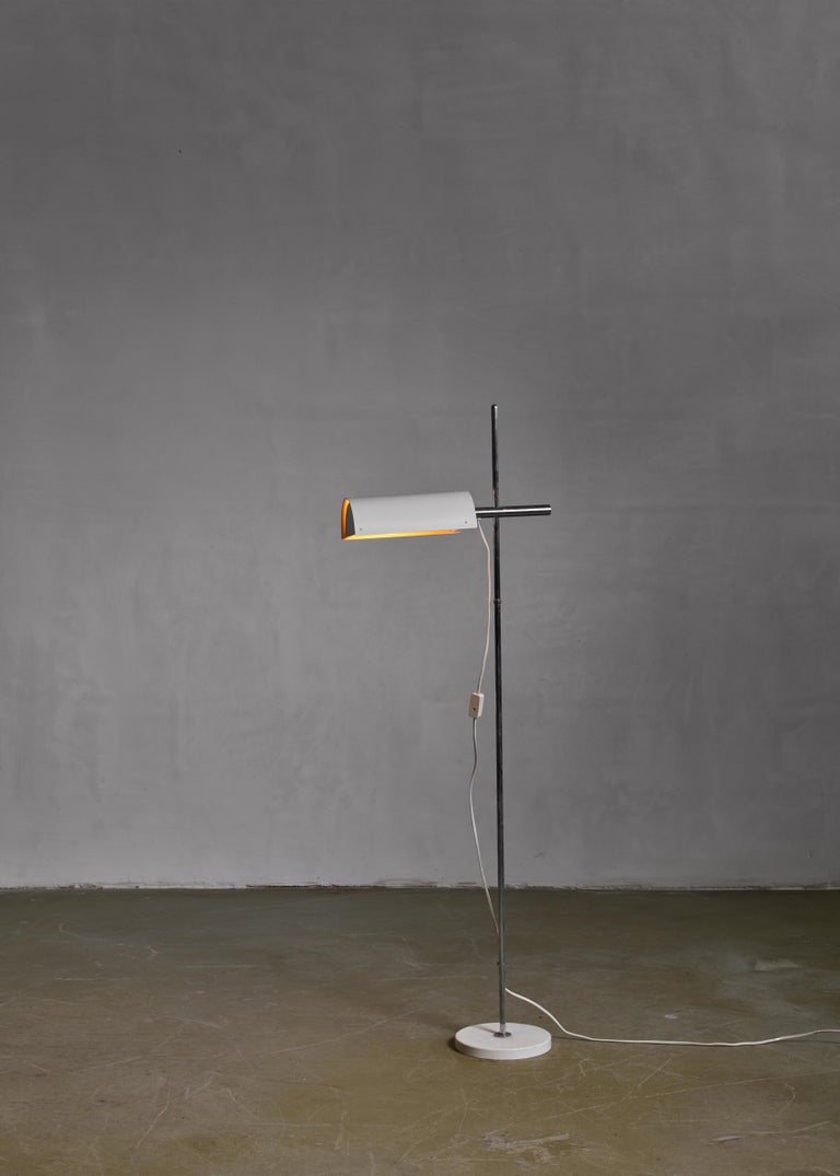 An adjustable floor lamp designed by Ben af Schultén for Artek. The lamp has a height-adjustable and swiveling white lacquered aluminum shade on a chrome stem.  This piece is old stock, never used stock from the Italian Finn Form collection. This