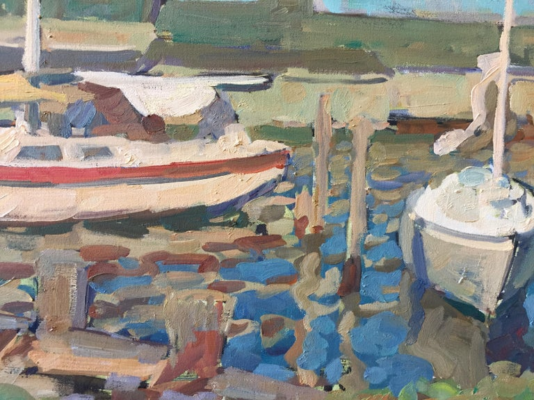 An oil painting of a marina in Greenport, on the North Fork of Long Island, New York. Bright blues and subtle reds and browns create this beautiful, realistic, impressionist painting. Two sailboats at rest in the water.   Framed in an Italian,