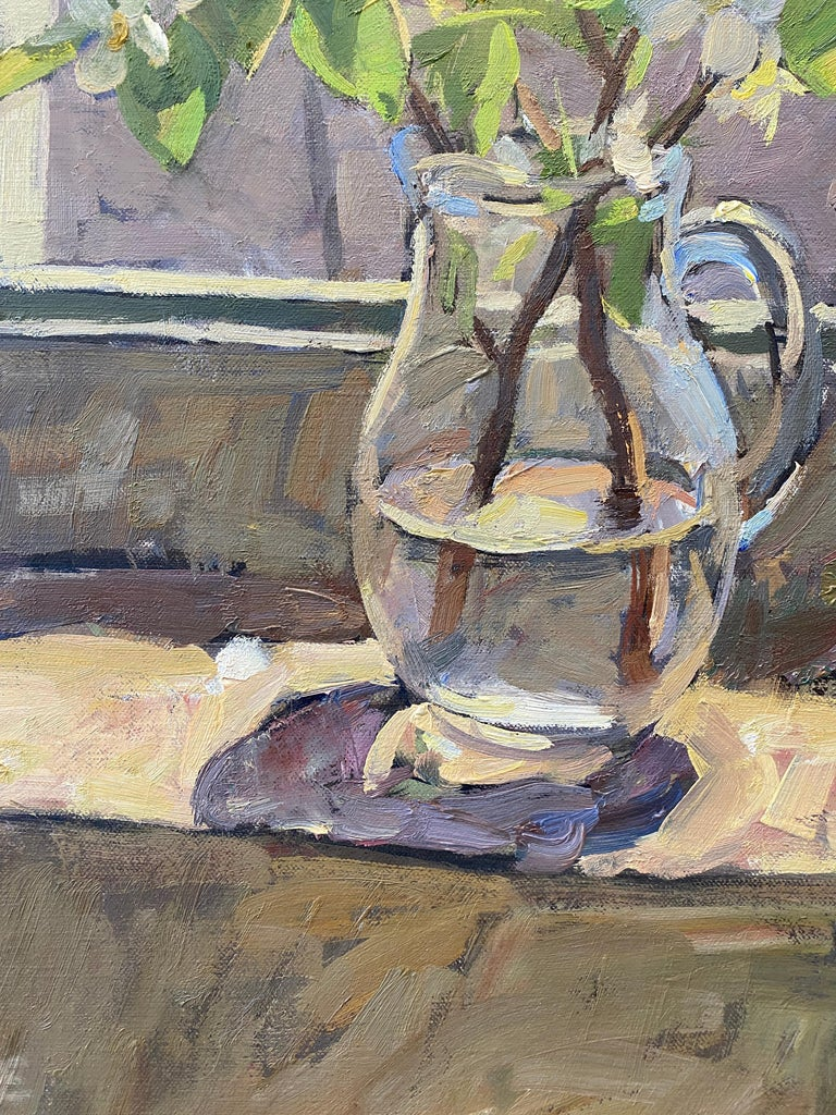 An oil painting that acts as both a still life, and an interior painting. A glass pitcher holds a pair of branches from a pear tree, flowering white pear blossoms reach upward amidst large green leaves. A glass paned window half open, gives fresh