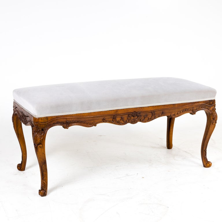 Baroque style bench standing on S-shaped curved volute feet. The frame has multiple curvatures and is decorated with carved shell and tendril decoration. The bench has been newly covered with a silver-grey velvet fabric.