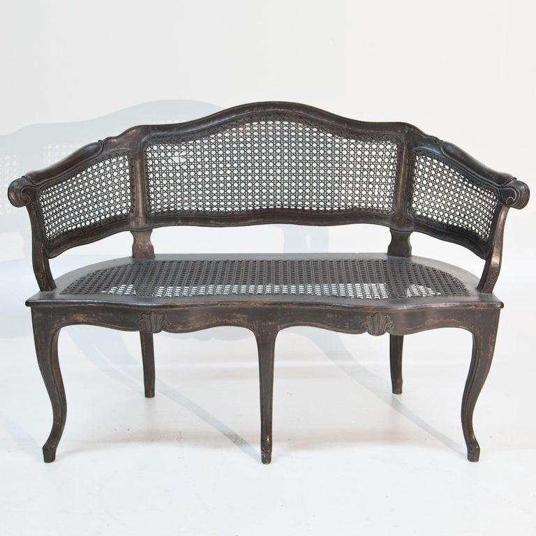 Bench with rocaille and shell decoration standing on five curved legs. The three-part backrest sinks in waves towards the sides and is covered with wickerwork like the seat. The grey setting is new and has been given an antique patina.