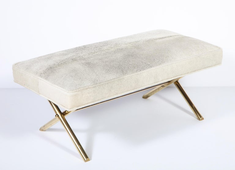 Decorative brass leg bench with upholstery in a cow hide, circa 1950. The upholstery is new.
