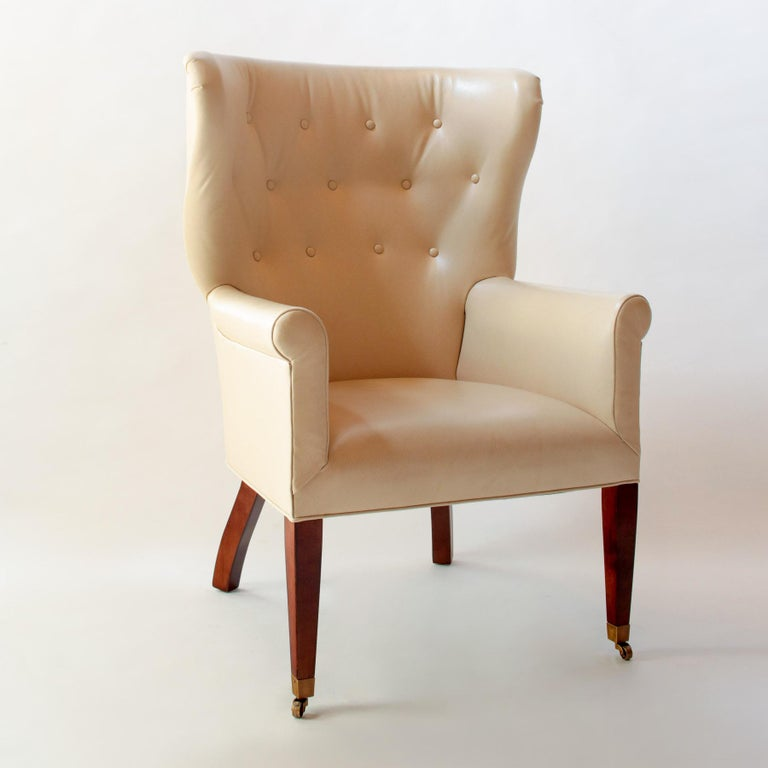 Contemporary/Transitional Georgian style tufted barrel back wing chair with legs in a mahogany finish, the front two legs terminating in brass casters. Upholstered in custom-colored Wagon Lit Edelman embossed leather.