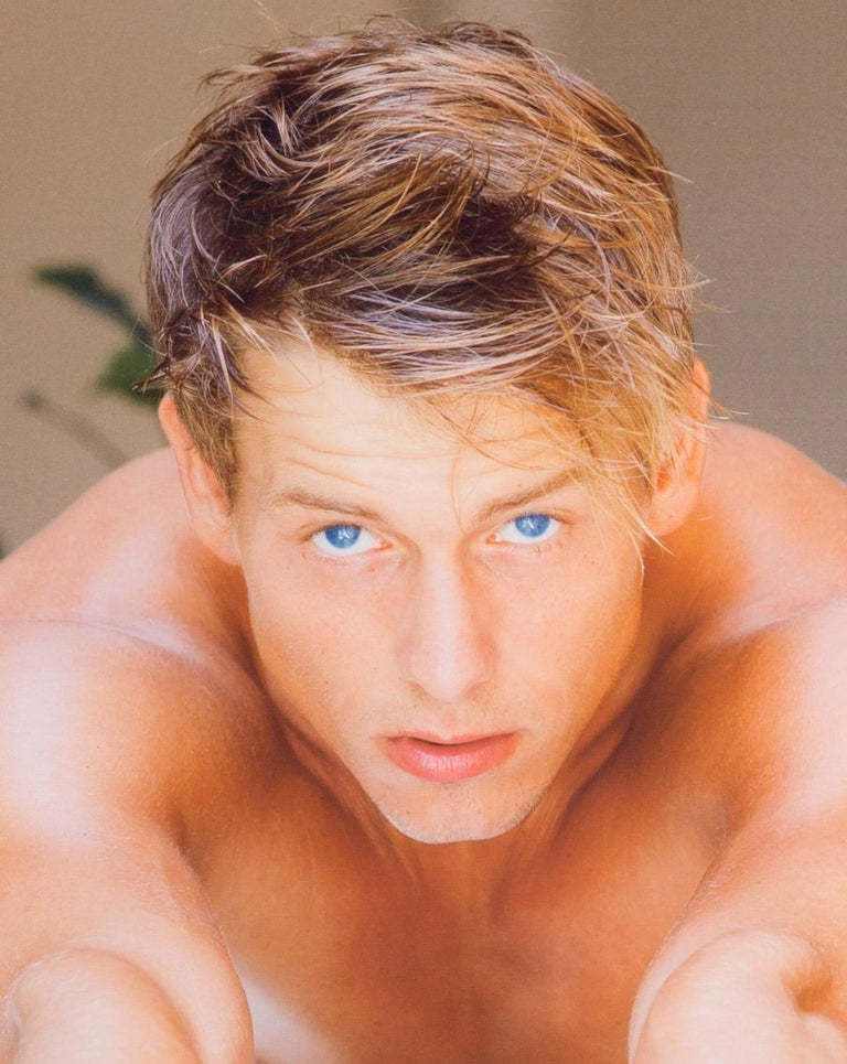Blue Eyes (hypnotic close up gaze of Bel Ami male model leaning cross a table) - Photograph by Benno Thoma