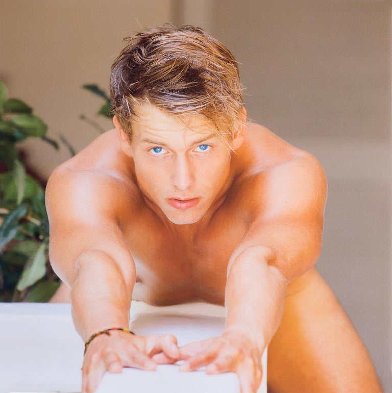 Benno Thoma Figurative Photograph - Blue Eyes (hypnotic close up gaze of Bel Ami male model leaning cross a table)