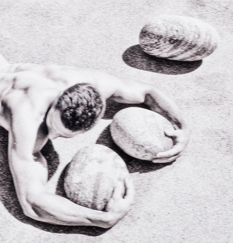 Rocks (nude model from Bel Ami lies prone with rocks in Greece) - Contemporary Photograph by Benno Thoma