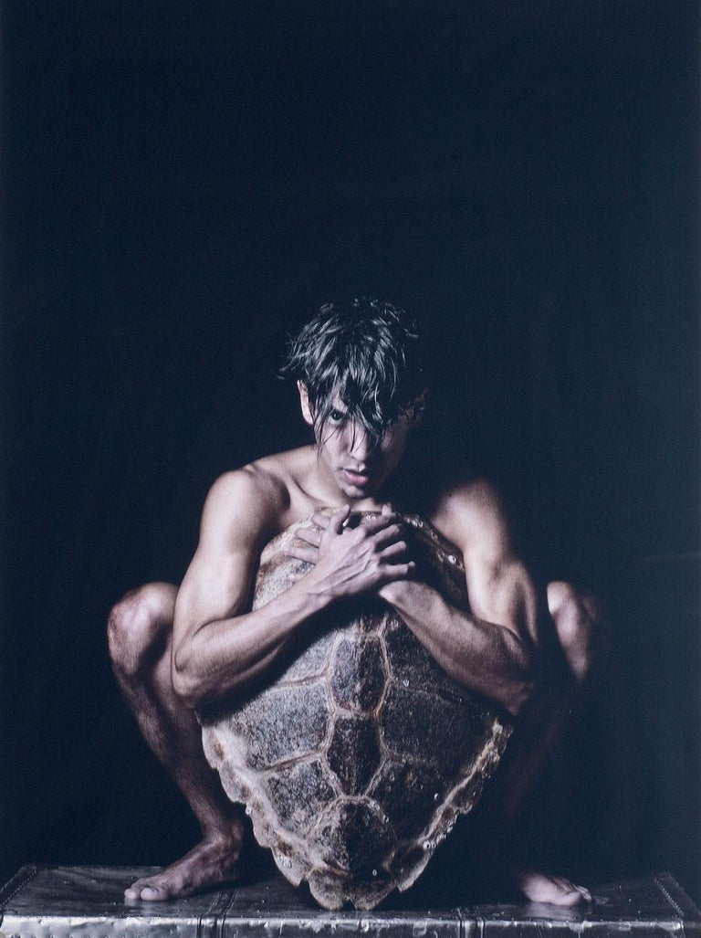 Benno Thoma Nude Photograph - Turtle (male model uses shield carved from large turtle shell to cover his body)