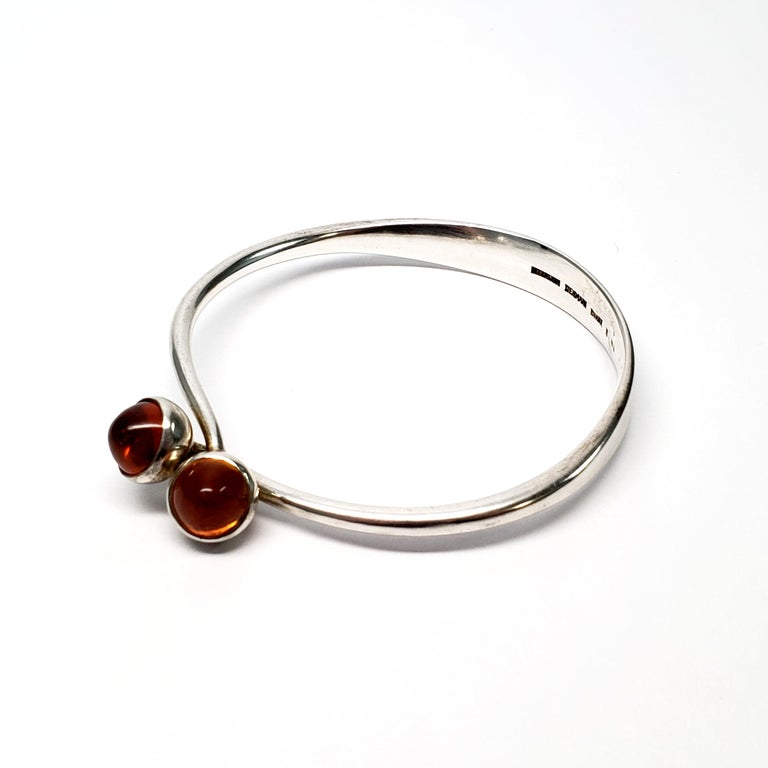 Vintage Bent Knudsen sterling silver and amber cabochon bangle bracelet.  Interlocking sterling silver bangle bracelet, by Bent Knudsen of Denmark, featuring 2 round, high set amber cabochons. Circa 1956.  Size: measures 7 3/4
