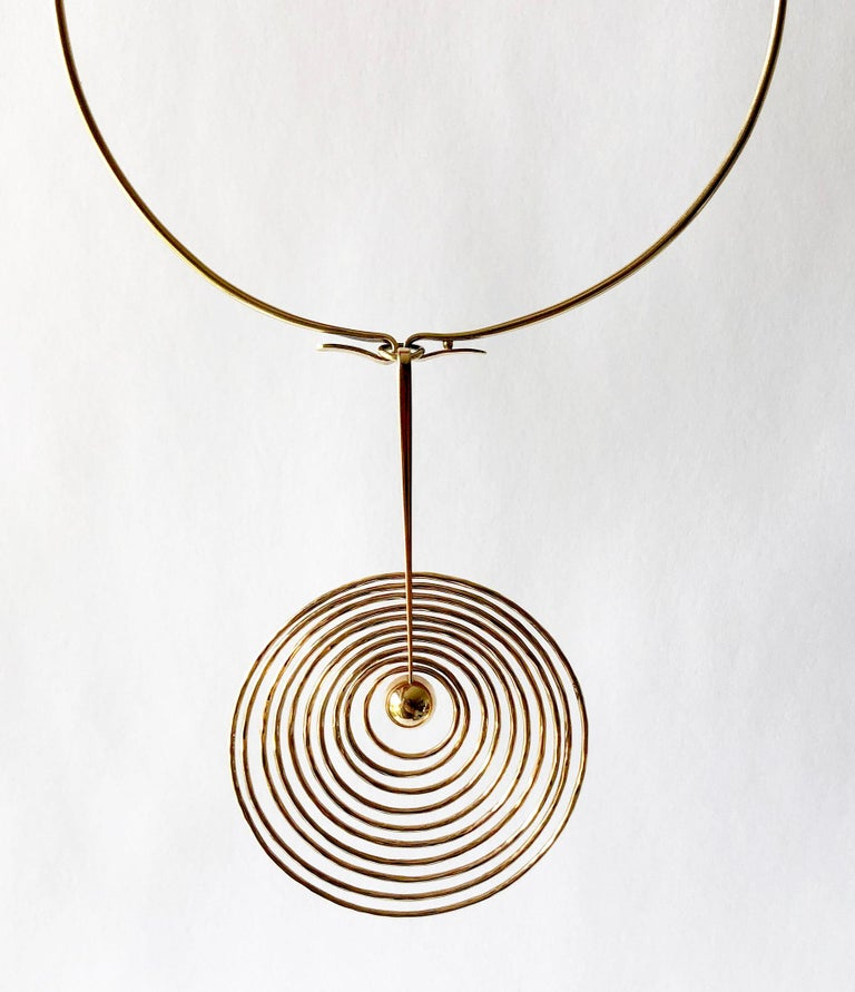 A 1960s 14k gold kinetic concentric circle pendant necklace and matching earrings created by Bent Gabrielsen of Denmark. The necklace torque measures about 15