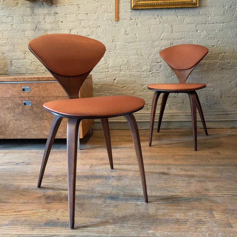 Pair of iconic, maple bentwood chairs by Norman Cherner for Plycraft feature burnt orange sheen upholstery on seat and back.