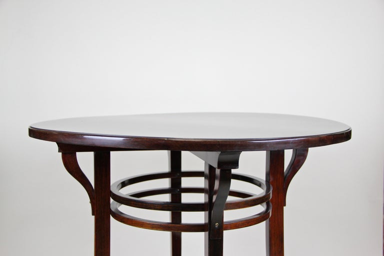Timeless bentwood side table by the famous company of Thonet Vienna/ Austria from the early 20th century, circa 1905. The round table comes with a great design and shows an extra small floating compartment in the lower third. The table top is