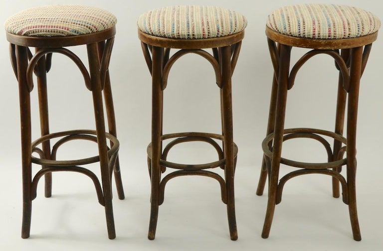 Nice group of 3 bentwood stools, attributed to Thonet. Each stool has been recently reupholstered in earth tone woven fabric, structurally sound and solid, cosmetic wear to wood finish, normal and consistent with age. Offered and priced