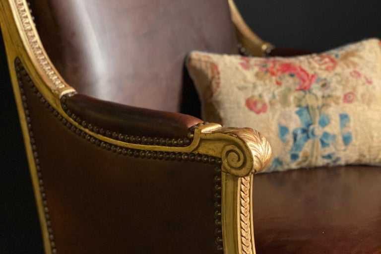 Gilded wood Louis XVI bergère with the gilding restored and the seats and backs newly upholstered in leather, a cushion was made using the original needlepoint upholstery. Stamped.
