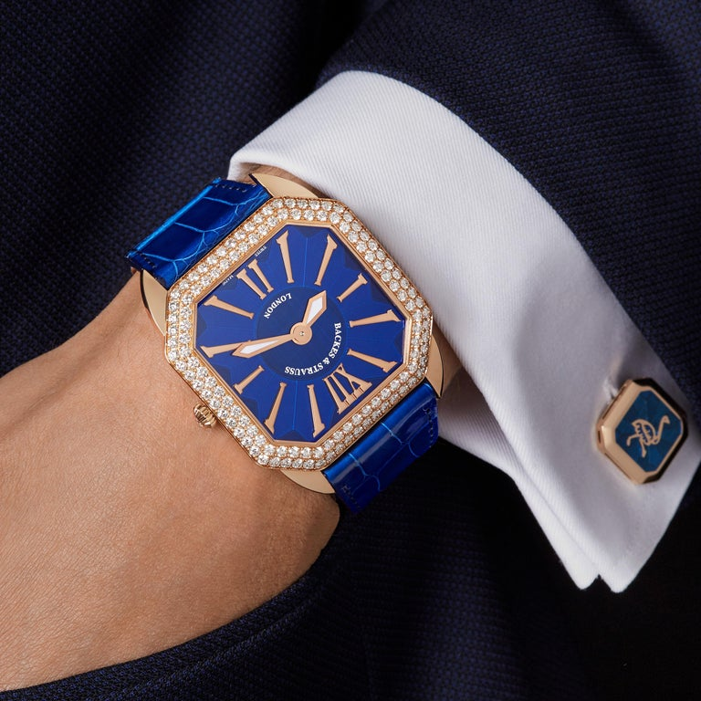 Berkeley Renaissance 43 is a luxury diamond watch for men crafted in 18kt Rose gold, featuring a blue square dial with rose gold roman numerals, mechanical movement. The crown, buckle and case are set with white Ideal Cut diamond. It is a 43 mm