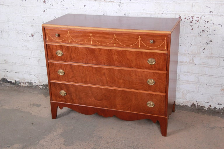 A gorgeous antique mahogany French style dresser by Berkey & Gay, circa 1930s. The dresser features beautiful mahogany wood grain and nice inlaid details. It offers ample storage, with four deep dovetailed drawers. Brass hardware is original, and