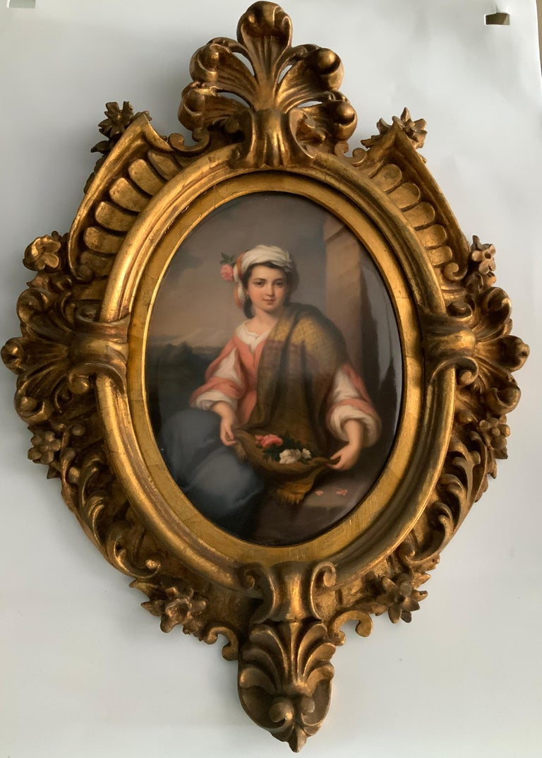 A porcelain plaque portrait from KPM that depicts a young girl sitting in a stone bench after gathering some roses in her shawl and embellish her turban with one of them. Beautifully carved gilt frame that features Prince of Wales feathers, acanthus