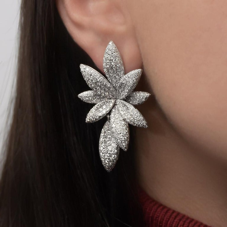 Crafted by Bernard Grosz in 18KT white gold these magnificent flower earclips are set with 840 round brilliant diamonds totaling 6.81 carats.  The flowers are composed of eight petals and the ninth petal is a drop that is detachable. The petals are