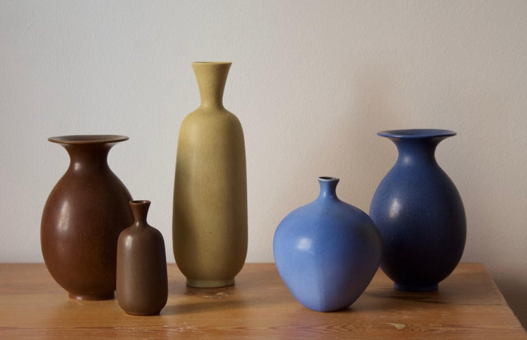A group of 5 organically shaped vases, all with simple monochrome glazing. Designed by Berndt Friberg for the Swedish firm Gustavsberg. Some with paper labels and stickers to backside.   Stated dimensions are off the tallest brown vase.  Other