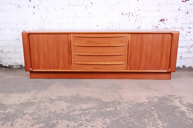 An exceptional midcentury Danish modern teak sideboard or credenza by Bernhard Pedersen & Son. The credenza features gorgeous teak wood grain and sleek Danish design. It offers ample storage, with seven dovetailed drawers and two shelves. The