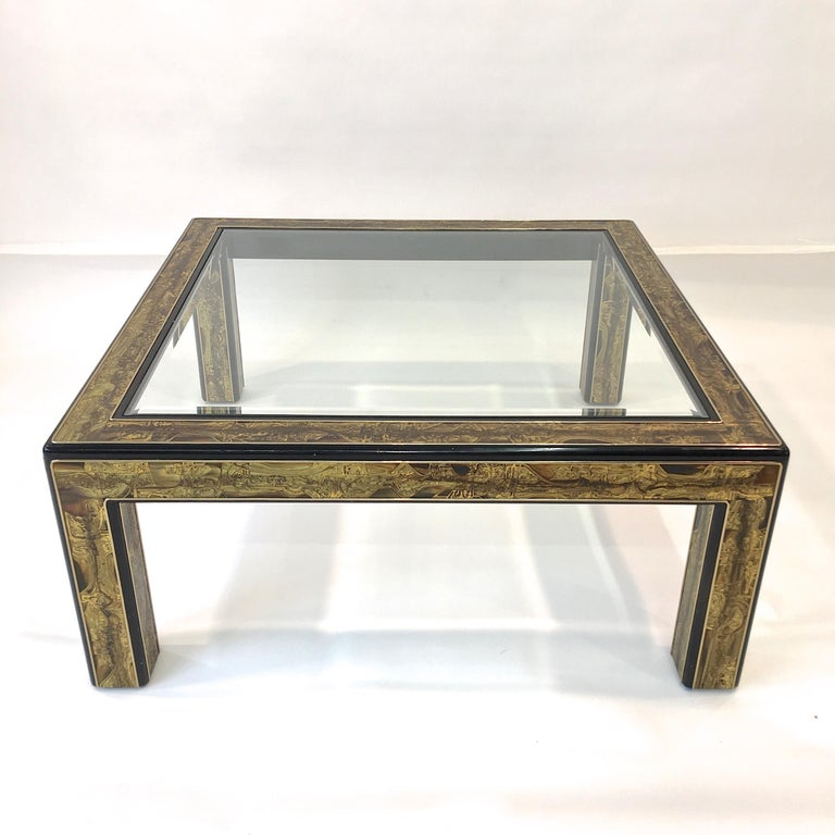 A square cocktail table created by metal sculptor Bernhard Rohne for Mastercraft circa 1970 in acid etched brass with ebonized wood and inset bevelled glass top.  See dining table version in late 1970s issue of H&G magazine: image # 20.  From
