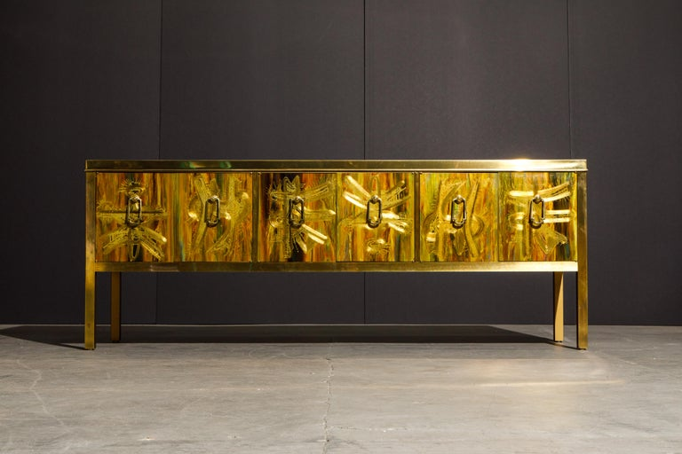 This incredible acid etched brass console cabinet was designed by Bernhard Rohne and produced by Mastercraft in the 1970s. Exquisite acid-etched artwork on the top, sides and front door panels with patinated brass trim and legs. Six doors and door