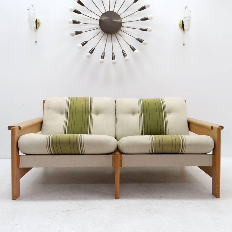 Bold and comfortable Danish modern two-seat sofa by Bernt Petersen, Denmark, 1970, oversized oak frame with dual colored cushions on canvas with leather straps.