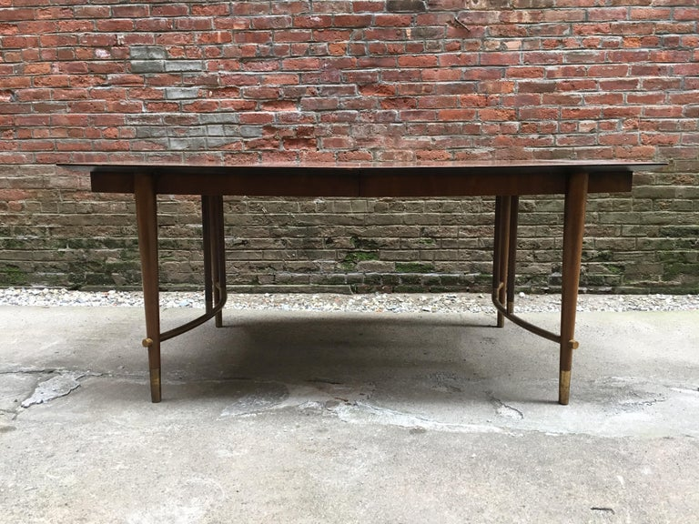 Stylish dining table designed by Bert England for Johnson Furniture Company, grand rapids, Michigan, circa 1960. Beautiful figured walnut veneers with brass base accents and sabots. Three extension leaves for more space and guests. Very good