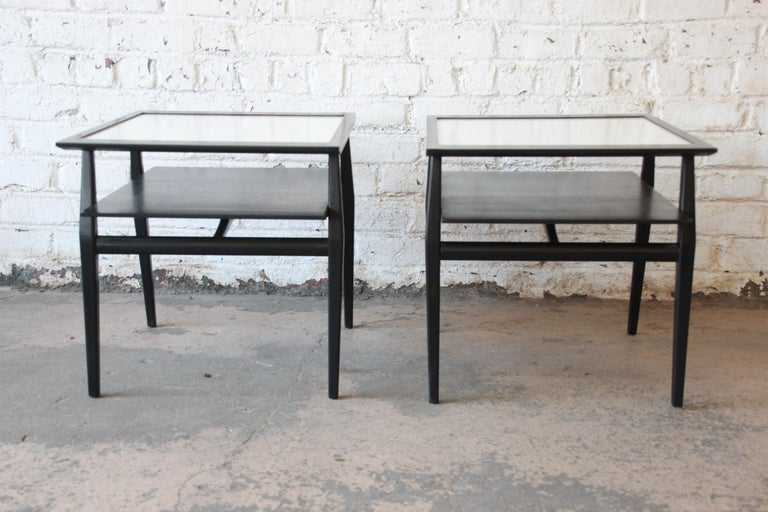 An outstanding pair of two-tiered side tables or nightstands designed by Bertha Schaefer for Singer & Sons. The tables feature sleek mid-century design with dramatic angular lines. The solid walnut frames have been newly ebonized, and they have